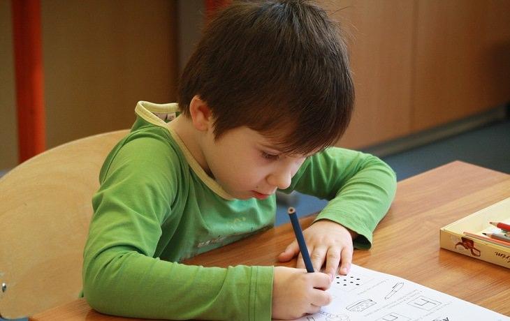 ילד מצייר ציור עם דף ועפרון