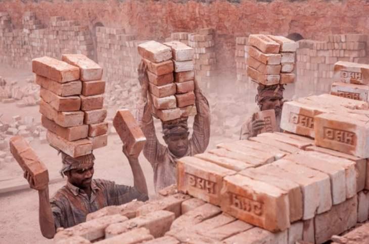 פועלים סוחבים לבני בניין על ראשם