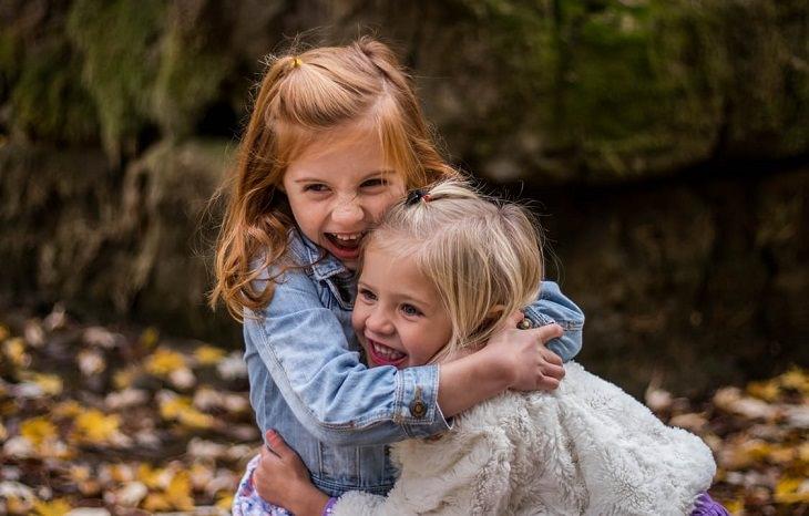 שתי ילדות קטנות מתחבקות ומחייכות
