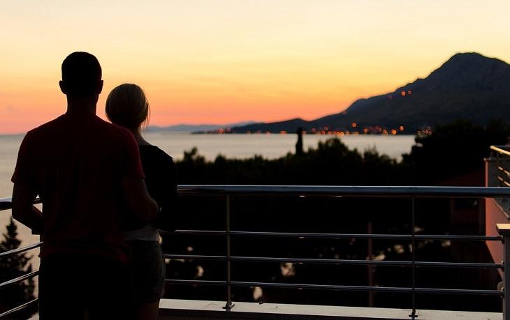 גבר ואישה צופים ממרפסת אל עבר נוף עם אגם והר