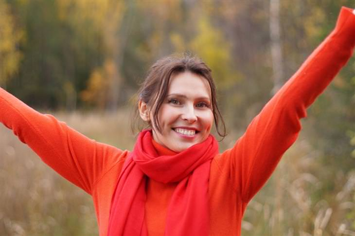 אישה מרימה את ידיה למעלה ומחייכת