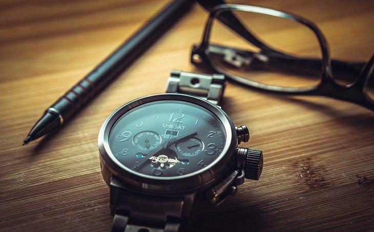 שעון יד מונח על שולחן ליד עט ומשקפיים