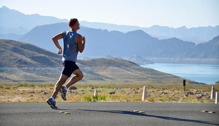 איש רץ מול נוף של אגם