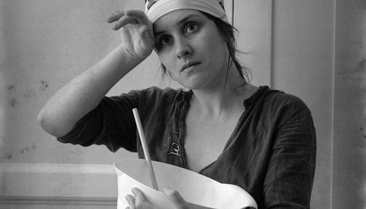 אישה מוחה זיעה מהמצח בזמן העבודה במטבח