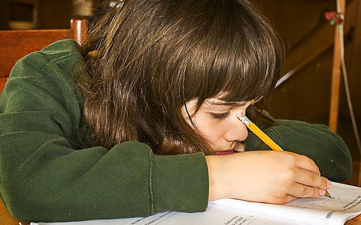 ילד עצוב מכין שיעורי בית
