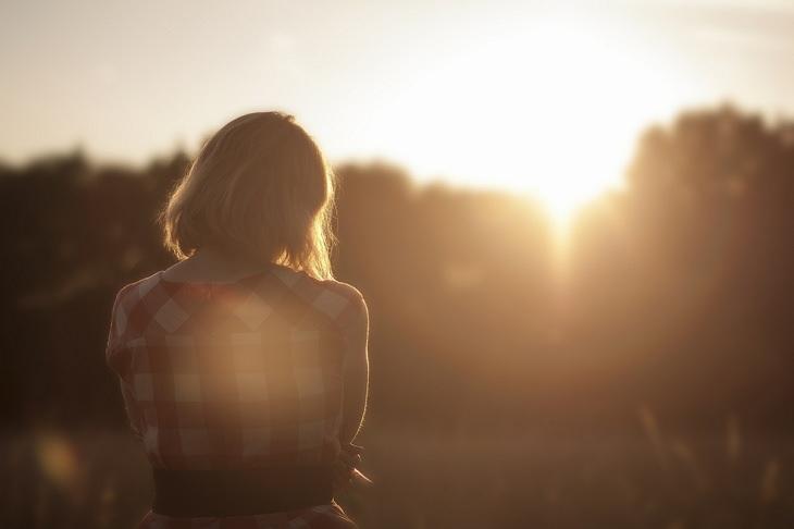 אישה מסתכלת על השמש שבאופק