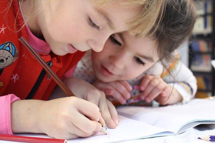 שתי ילדות רוכנות מעל ספר