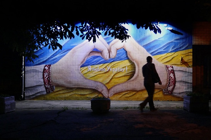 ציור קיר של שתי ידיים שמשלימות יחד צורה של לב