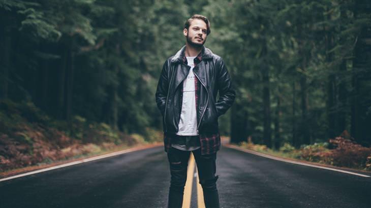 איש עומד באמצע כביש מוקף עצים