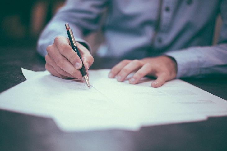 יד אוחזת בעט וחותמת על מסמך