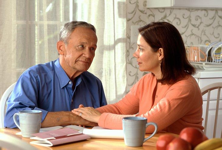 אדם מבוגר יושב ליד השולחן עם מבט מוטרד ואישה צעירה יותר לידו