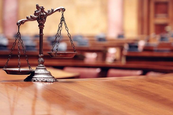 מאזניים כשברקע אולם בית משפט