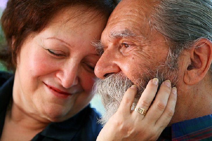 זוג מבוגרים נשוי, מחייך ונשען אחד על השנייה