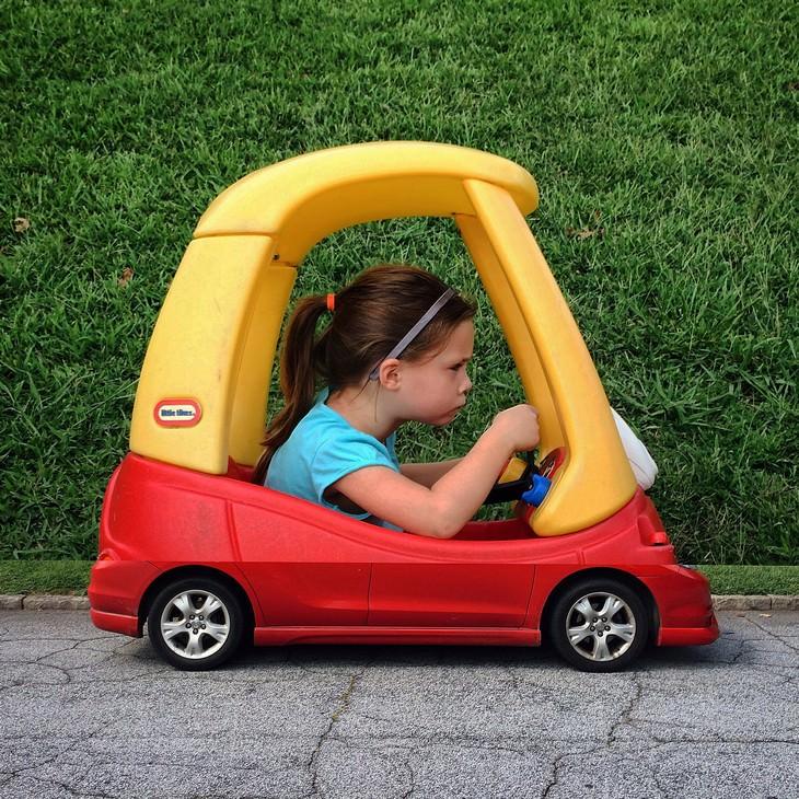 ילדה קטנה נוהגת בשילוב של מכונית צעצוע ורכב ספורט