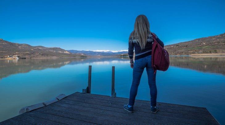אישה עומדת מול אגם