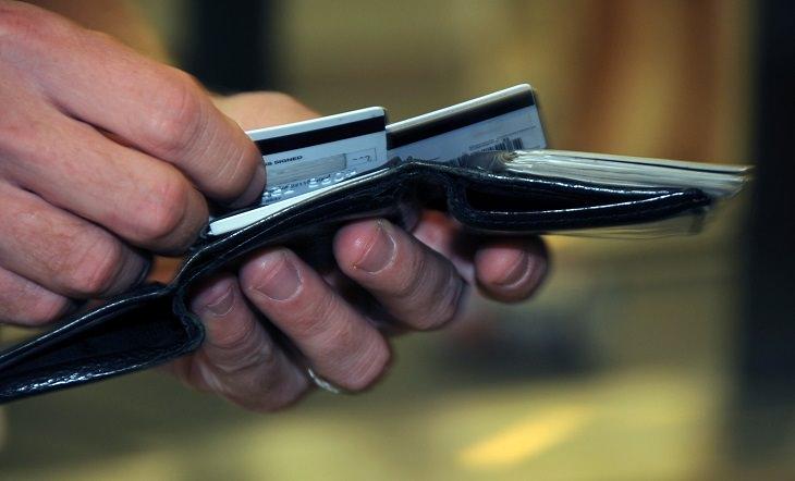 יד אוחזת בארנק ומוציאה כרטיס אשראי