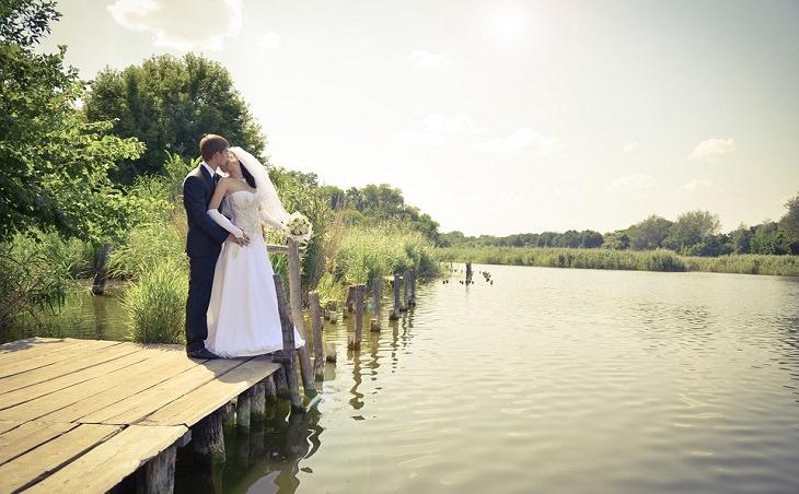 חתן וכלה מתנשקים על מזח עם נוף לאגם