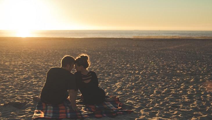 בני זוג יושבים על חוף הים ומצמידים את המצח אחד של השנייה