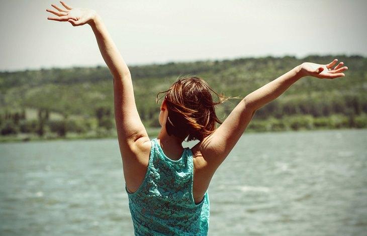 אישה מרימה ידיים למעלה מאושר