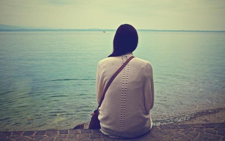 אישה יושבת על שפת אגם ובוהה באוויר