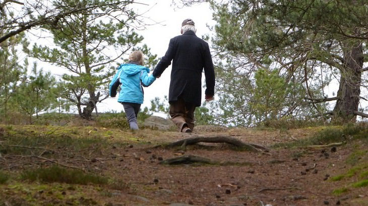 סבא ונכדה הולכים יד ביד בטבע