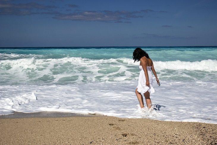אישה עומדת בתוך המים הרדודים שבים