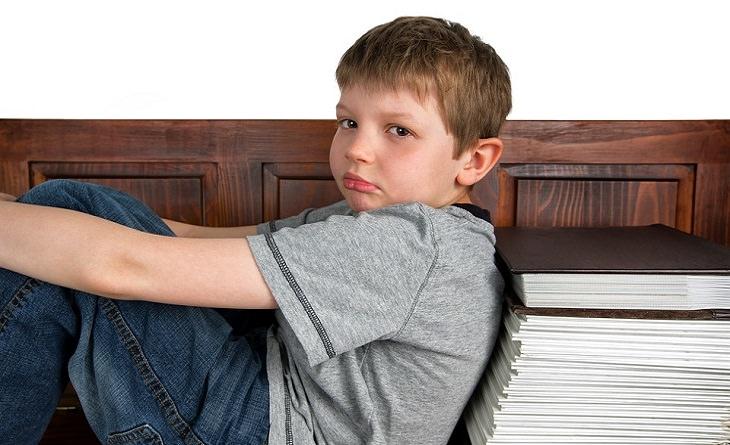 ילד ליד ערמת ספרים ענקית