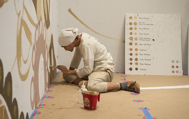 אסאי מחזיק מכחול ומצייר על הקיר