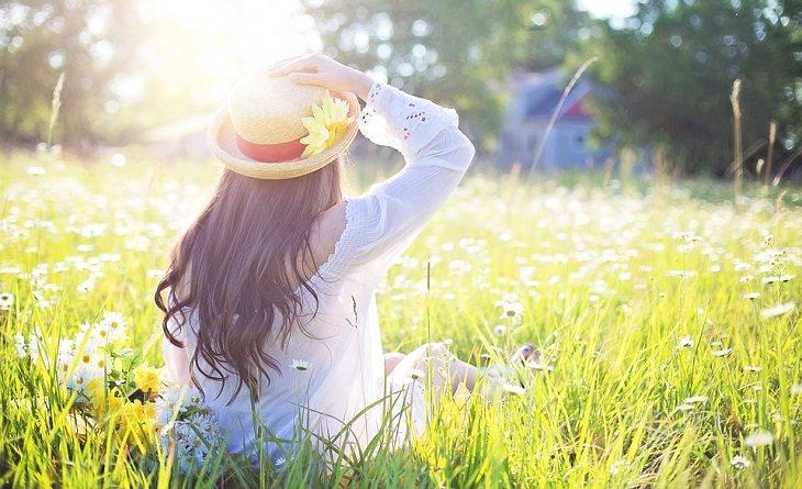 אישה יושבת על דשא ונהנית מהטבע ומהשמש