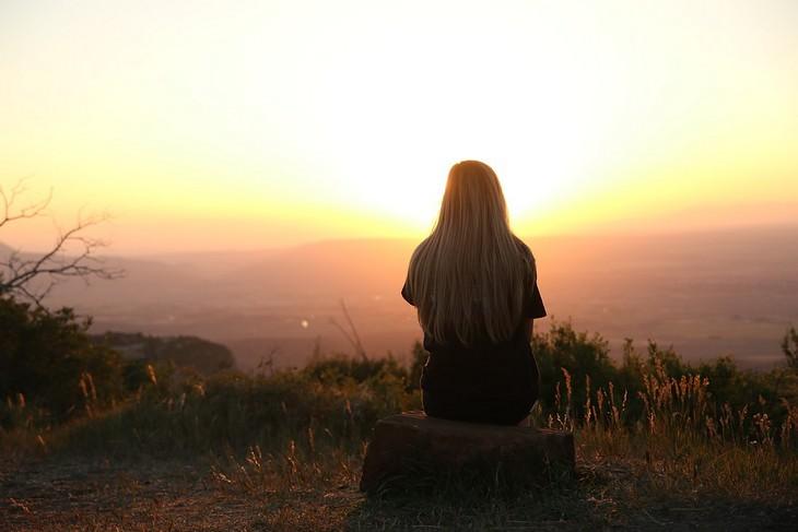 צילום מהגב של אישה יושבת על סלע מול השקיעה