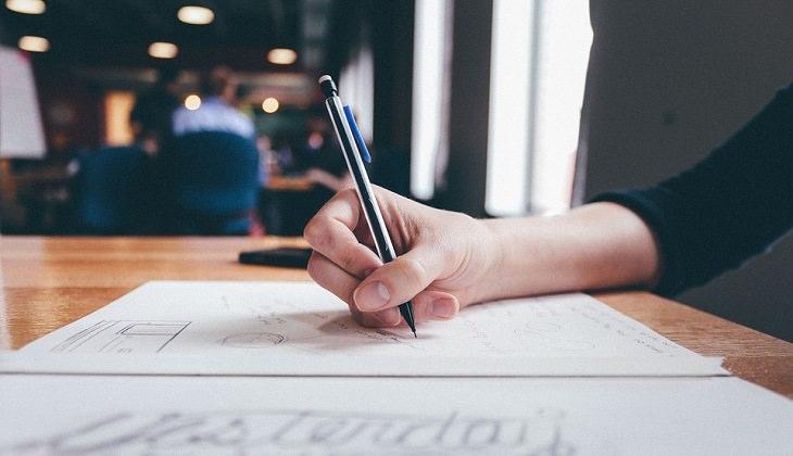יד רושמת על דף עם עפרון
