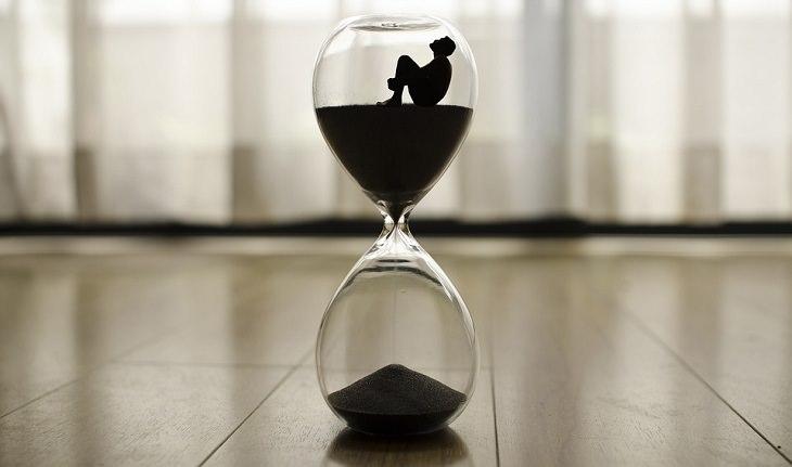 אדם יושב בתוך שעון חול