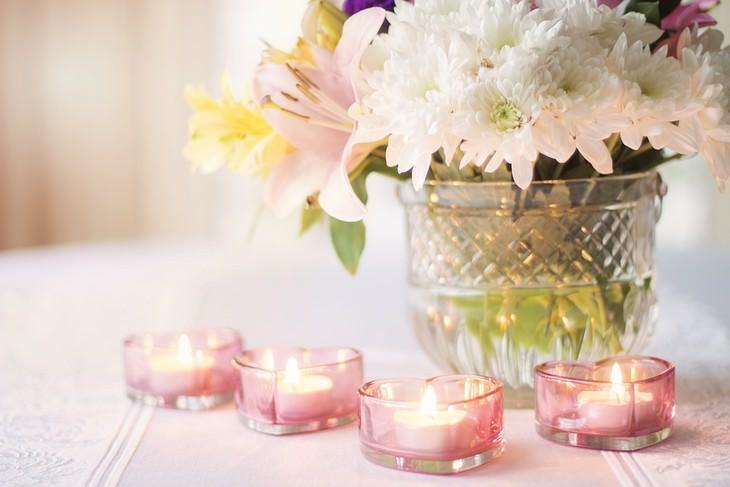 נרות דולקים בתוך כלים קטנים בצורת לב מול אגרטל עם פרחים