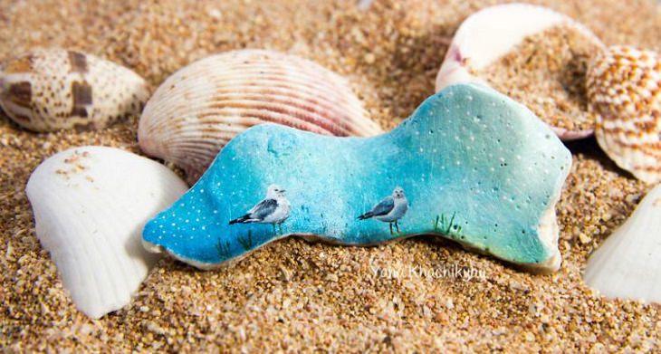 ציור של ציפורים על אבן קטנה ולידה צדפות