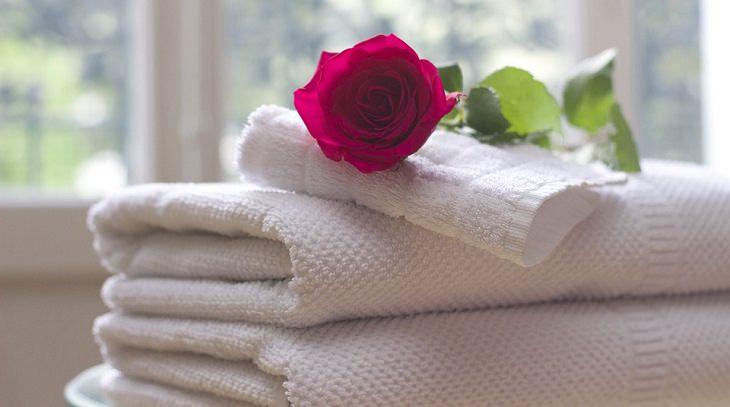מגבות מקופלות ועליהן ורד