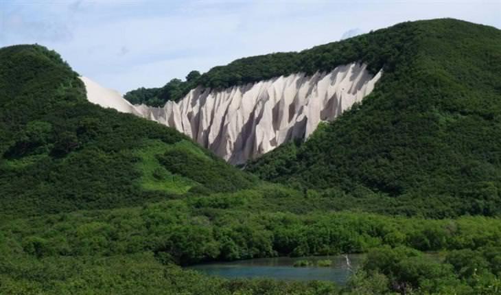 הרים מכוסים בעצים עם צוק בצבע לבן וצורה של דיונות חול