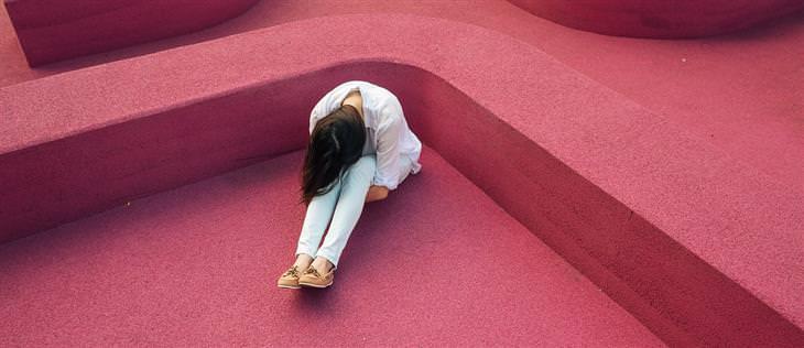 אישה יושבת על הרצפה עם ראש רכון ומחבקת את רגליה
