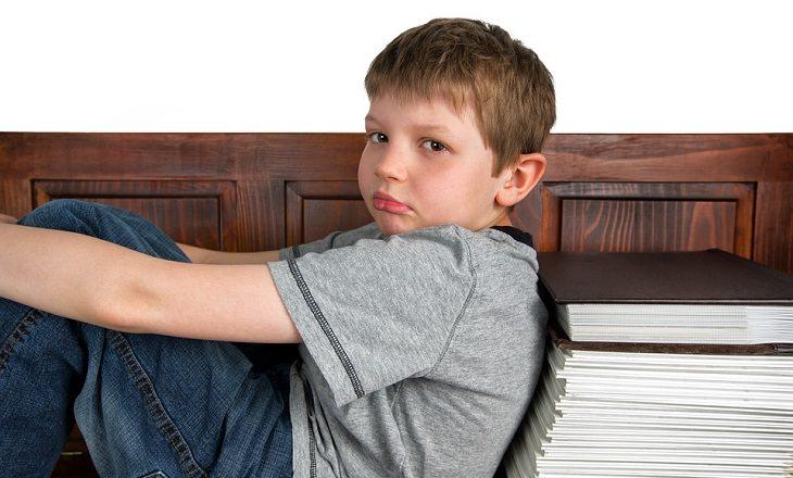 ילד עצוב ליד ערימת ספרים