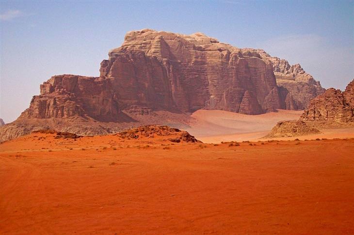 מישור של חול אדום וברקע צוק סלעי גדול בצבע אדום