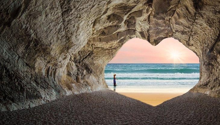 פתח של מערה בצורת לב שפונה אל החוף