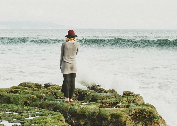 אישה עומדת לבדה מול הים