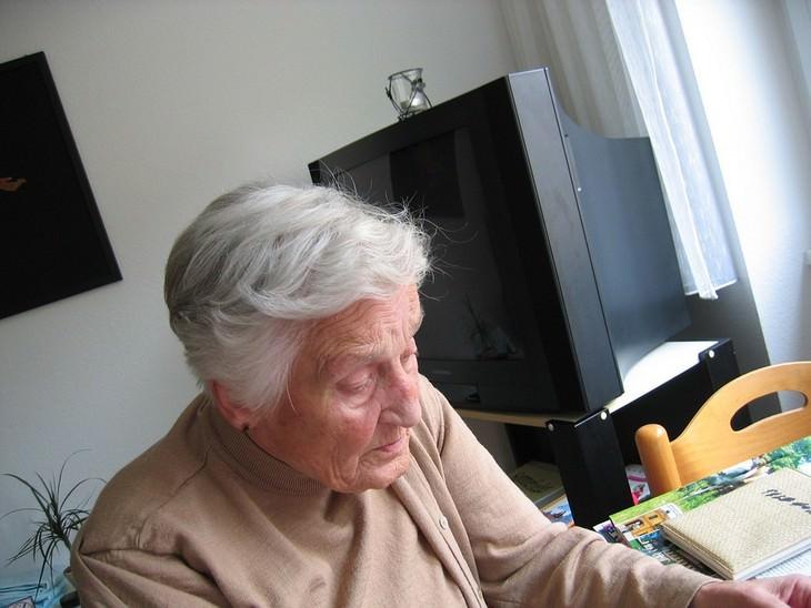 אישה מבוגרת יושבת ליד שולחן