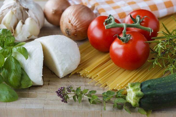 צרור עגבניות, בזיליקום ומוצרלה על קרש חיתוך מעץ