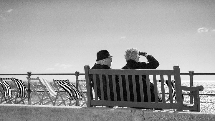 זוג מבוגר יושב על ספסל ליד הים