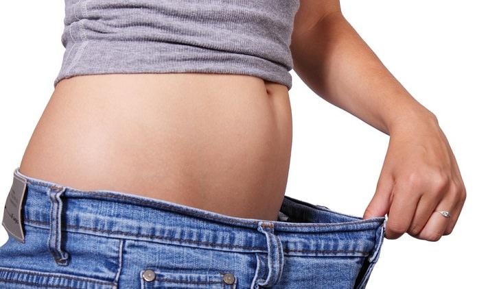 אישה אוחזת בג'ינס שגדול עליה