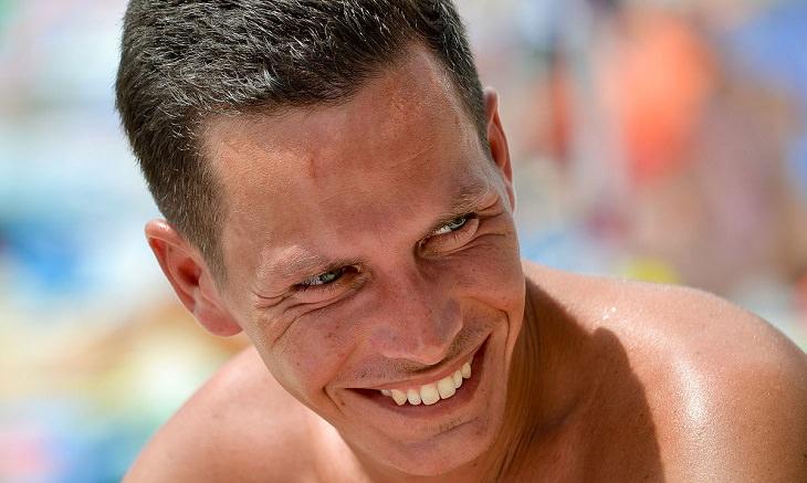 איש מחייך עם שיניים לבנות