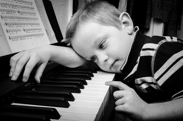 ילד משכיב את ראשו על פסנתר ולוחץ על אחד מכפתוריו