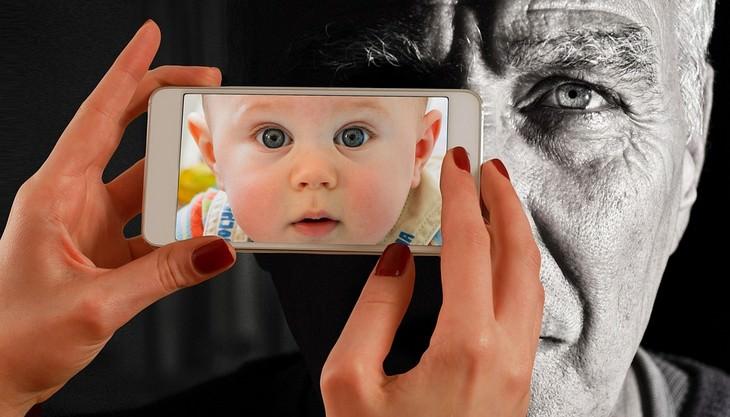 יד של אישה מצלמת גבר מבוגר כאשר במצלמה מופיע תינוק