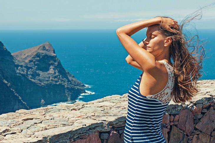 אישה מניפה את שערה ליד הים