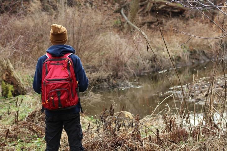 איש עם תיק גב עומד מול נחל